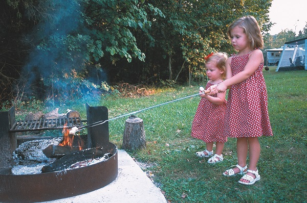 two toddler girls in matching dresses roasting marshmallows over a campfire