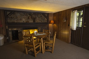 cabin interior with table, chairs and fireplace