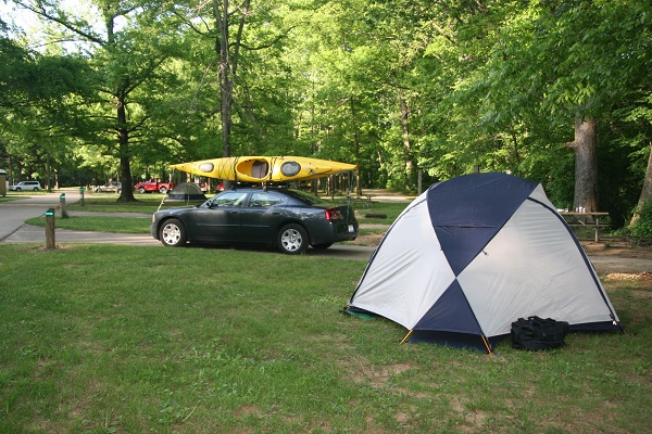a tent in the campground with a car and kayak in the background