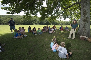 kids sit under the shade of a tree listening to the park naturalist who is holding a snake