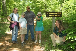 the park naturalist points out a plant on a guided hike with a family