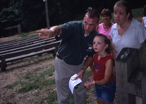 a park naturalist points out something to a family during an evening nature program