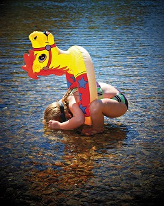 little girl bent over looking into water with goggles on and a horse shaped floaty around her waste