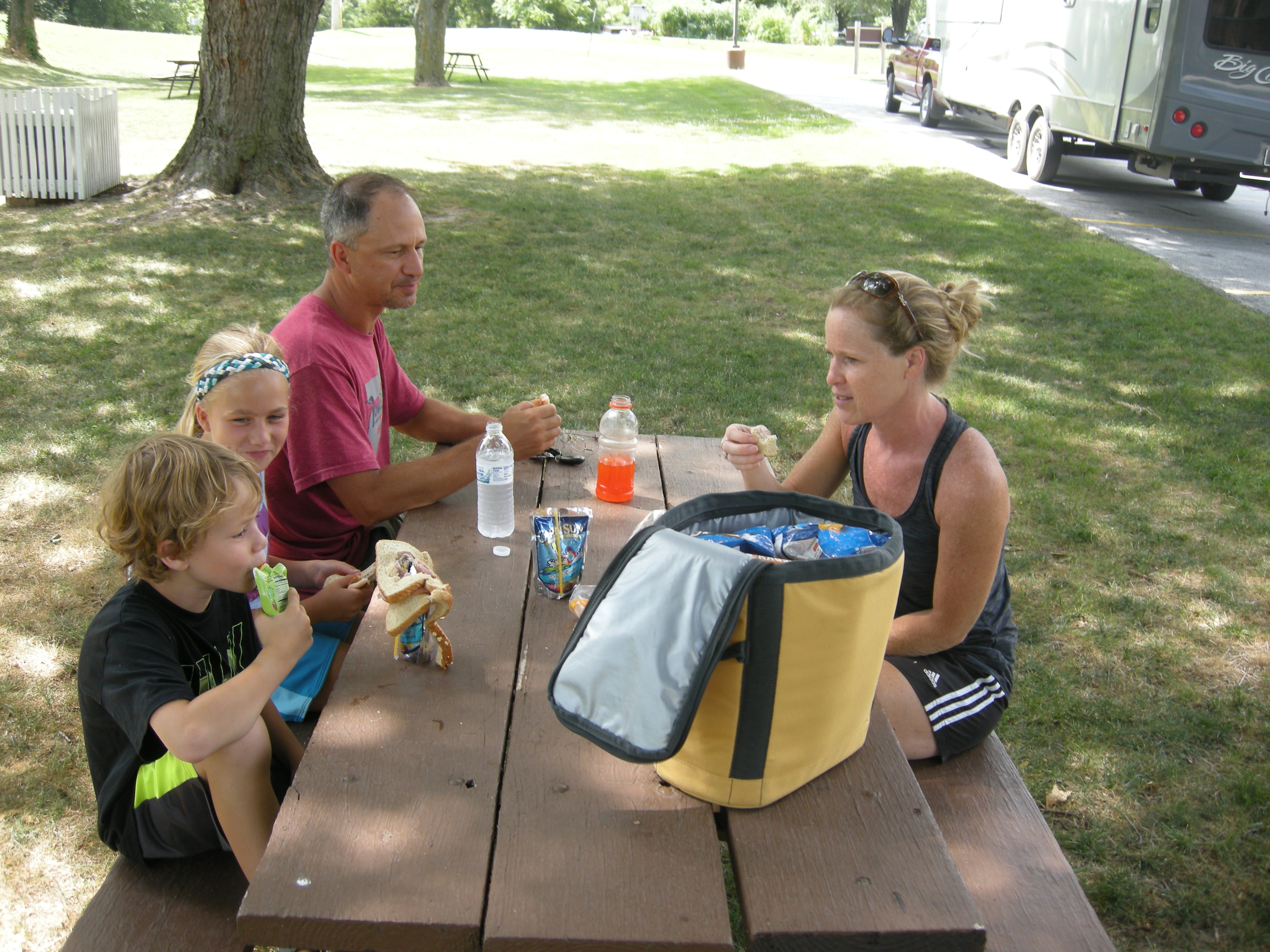 A family enjoys lunch at a picnic table