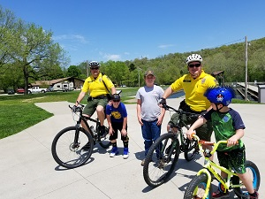 Two state park rangers on bicycles posing with three kids