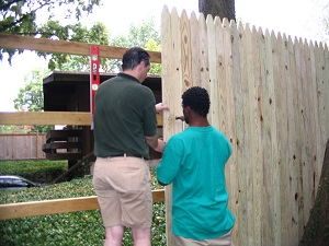 a park employee and a young seasonal employee building a wooden fence