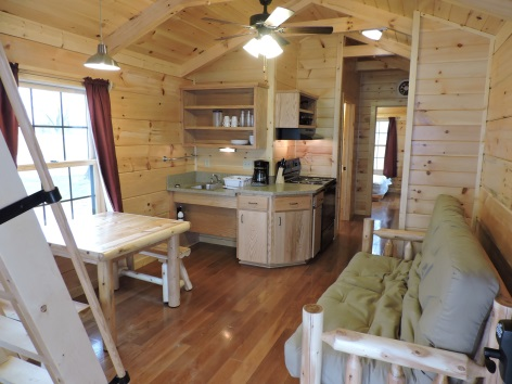 interior of cabin with kitchen area, table and futon