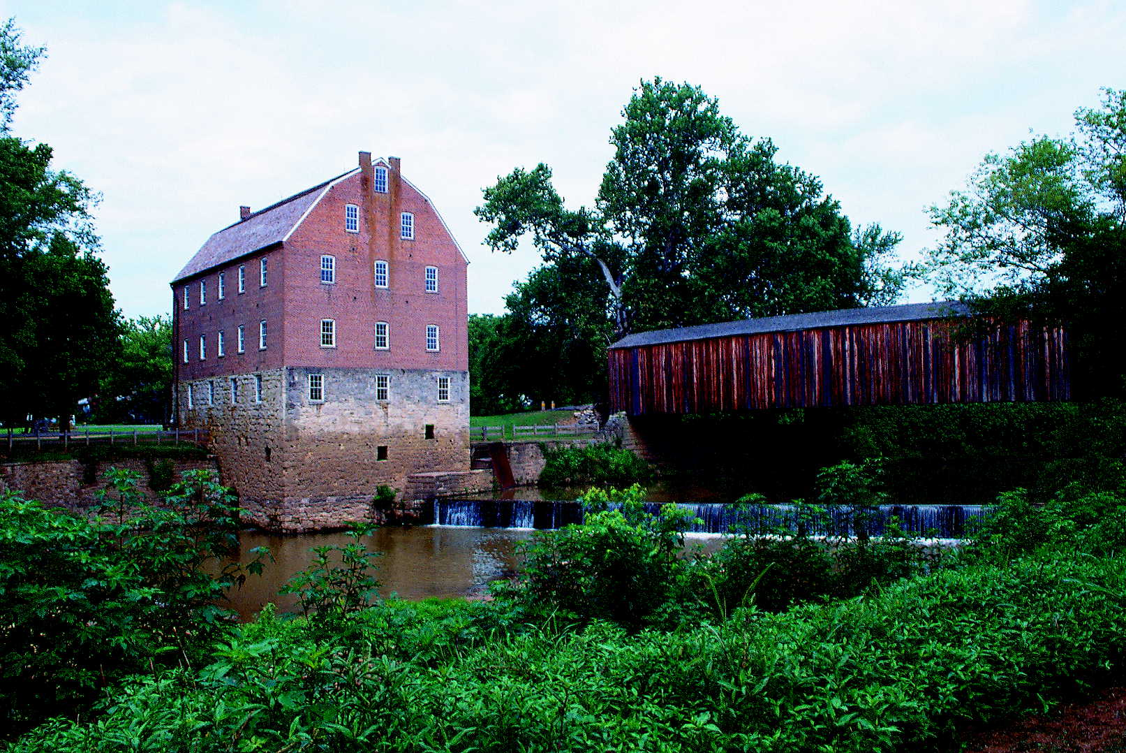 scenic view of the four-story red mill with the adjacent covered bridge with water cascading below