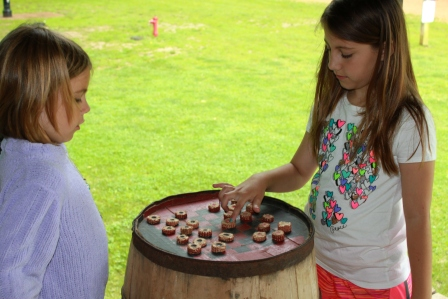 two girls playing checkers on top of a barrel