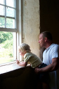 a man holds a small child so that he can see out the window of the mill