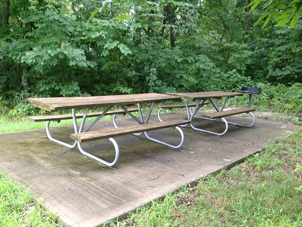 two picnic tables end-to-end on a concrete pad