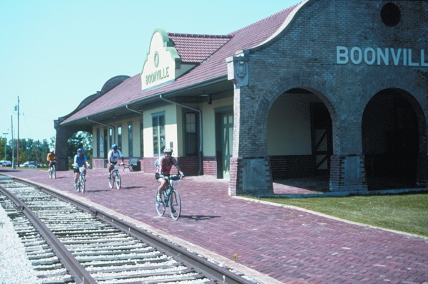 bicyclists riding next to railroad tracks in front of the Boonville Depot