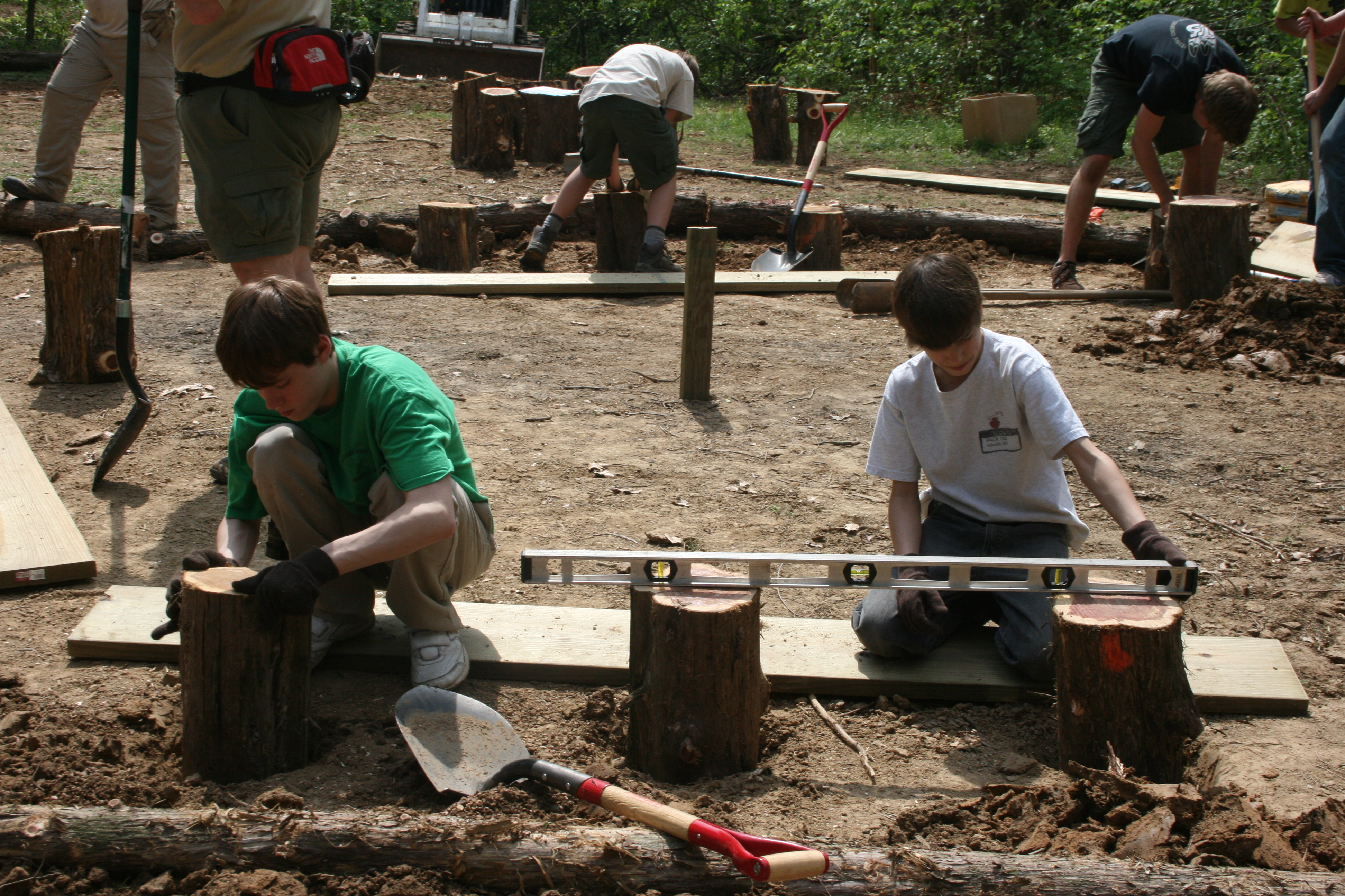 a group of Boy Scouts building benches