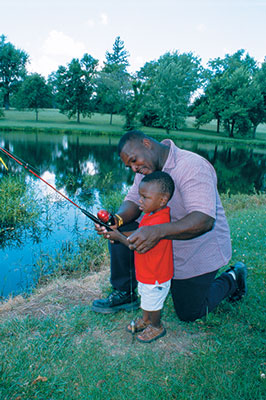a man helping his toddler son fish