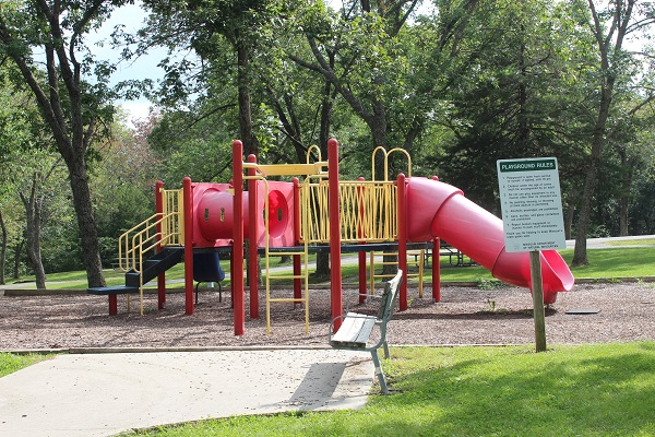 a bench sits near playground equipment with a few slides