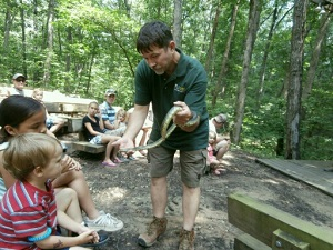a park naturalist shows two kids a snake