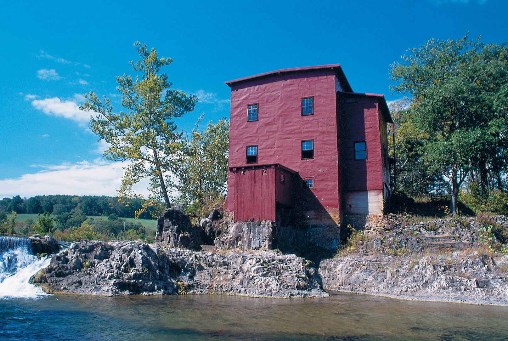 red mill with water cascading over a ledge next to it