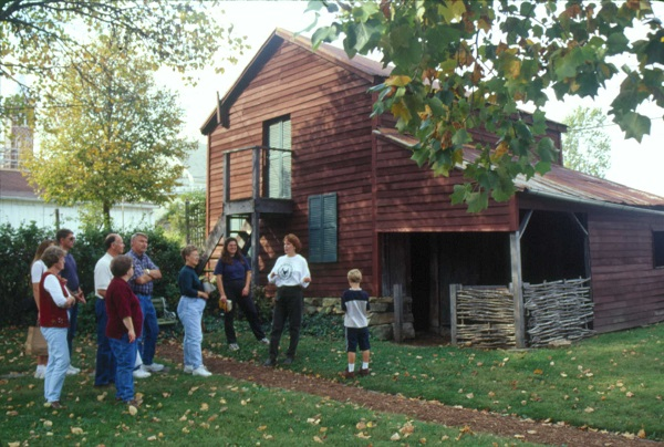 A tour group in front of an old barn at Deutschheim State Historic Site