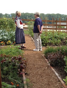 a tour guide with a lady walking through the site's gardens