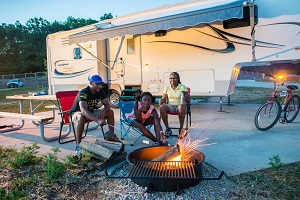 family sitting in front of camper around campfire