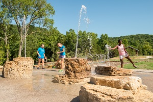 Kids playing in the water features of the playground at Echo Bluff State Park