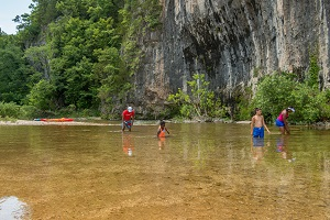 people swimming in the creek next to the bluff