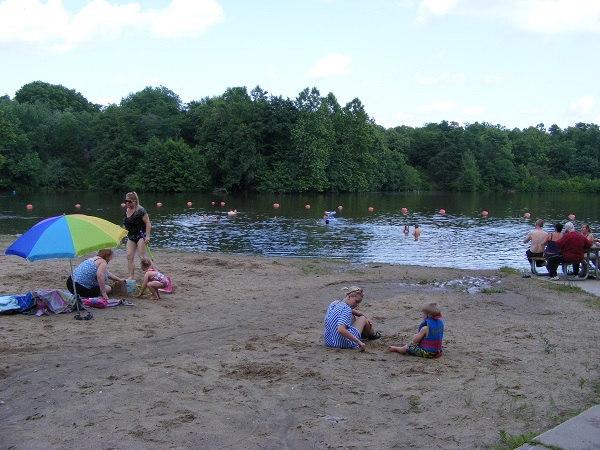 people sitting on the beach and swimming in the lake