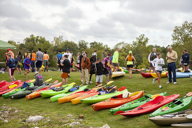 a row of colorful kayaks and people ready to participate in an event