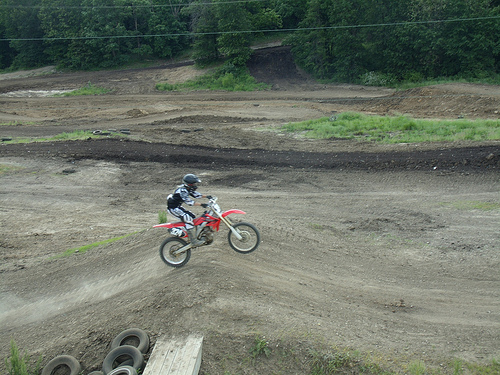 a guy on a dirt bike airborne on the motocross track