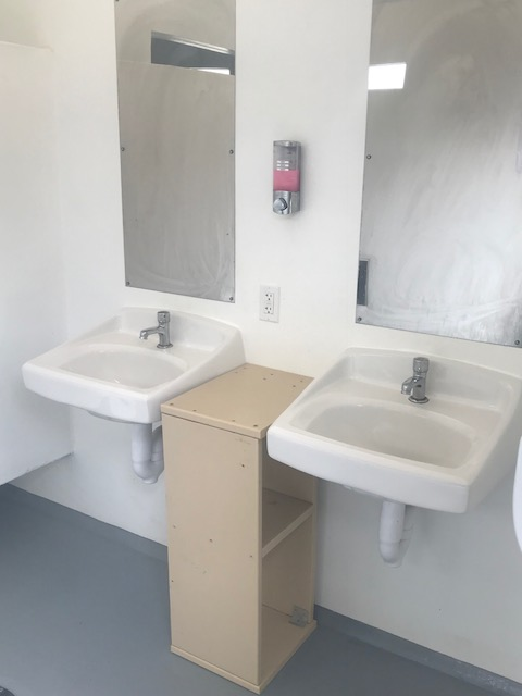 Two sinks, soap dispenser and outlet inside showerhouse