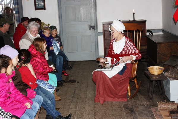 woman in period attire embroidering in front of a group of people