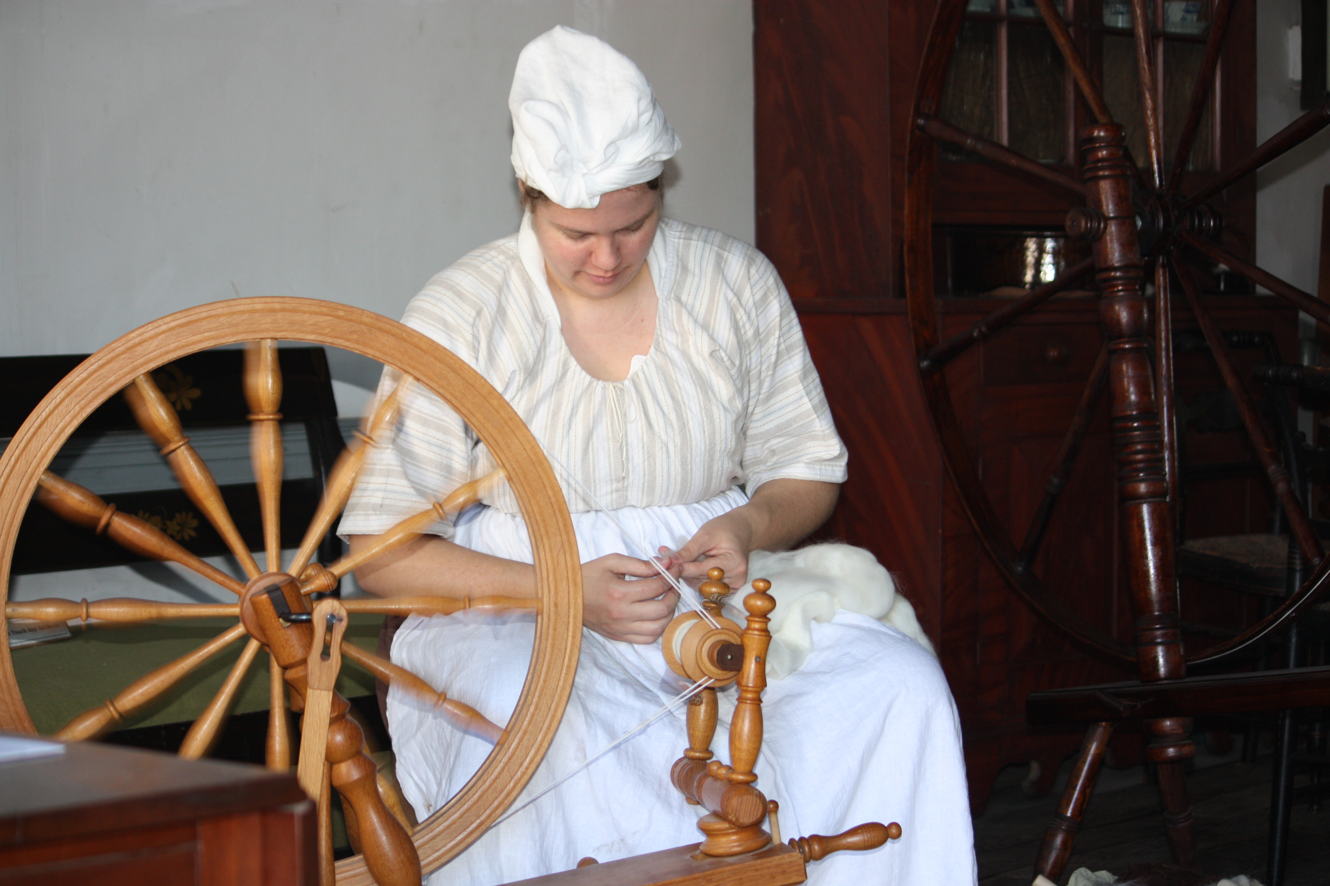 woman in period attire weaving with a spinning wheel