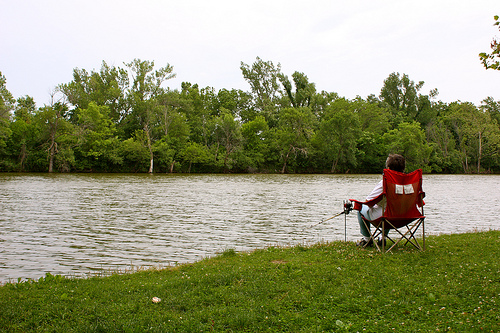 person in lawn chair fishing for the shore of the lake