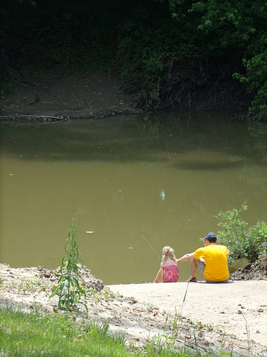 a father and daughter sit on the boat ramp and fish in the river