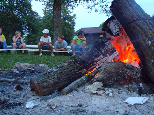 Kids sitting around a group fire ring.