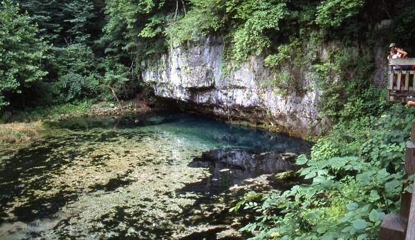 the blue water of the spring beneath a overhanging rock bluff