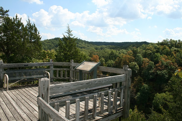 wooden overlook deck overlooking tree-topped hills