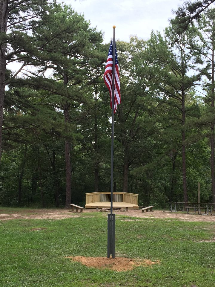 flag pole with flag and group fire ring area in the background