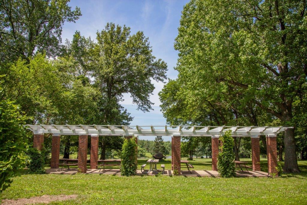 pergola with picnic tables under it