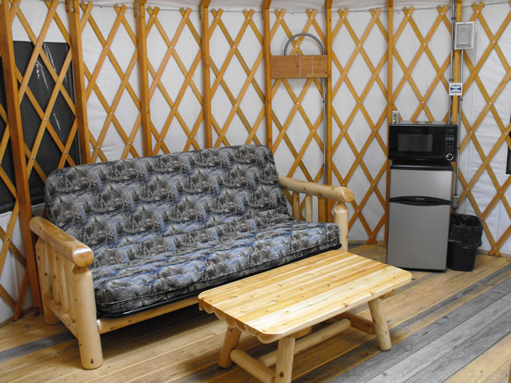 Futon and mini fridge and microwave inside the yurt