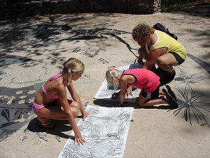 kids tracing concrete stamps onto paper