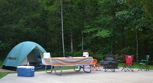 tent , a cooler and lawn chairs set up next to a picnic table on a campsite