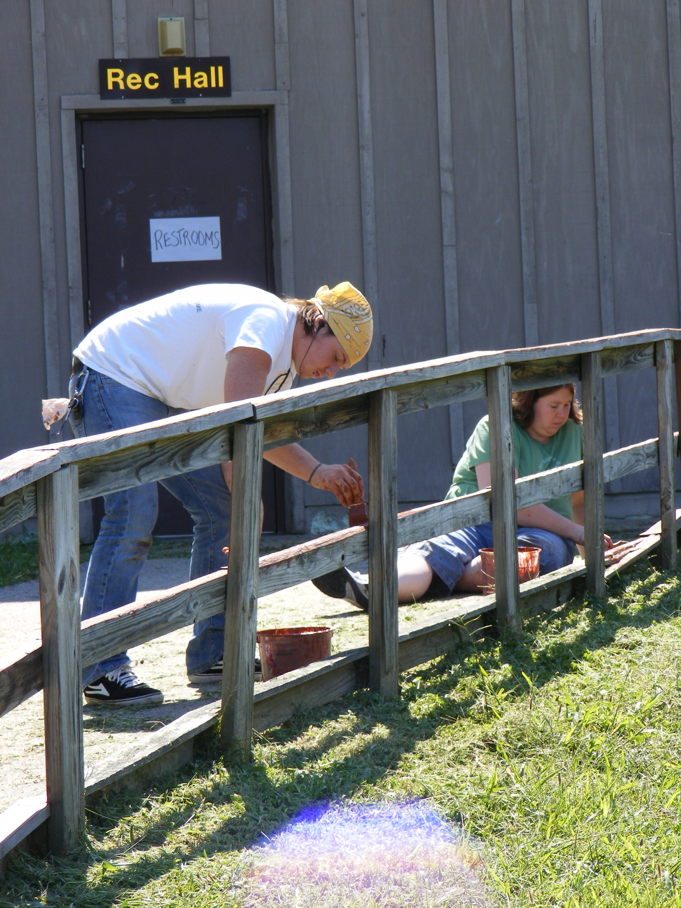two volunteers painting a fence