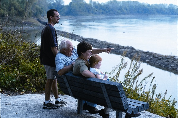 a group of people take a break on a bench overlooking the Missouri  River