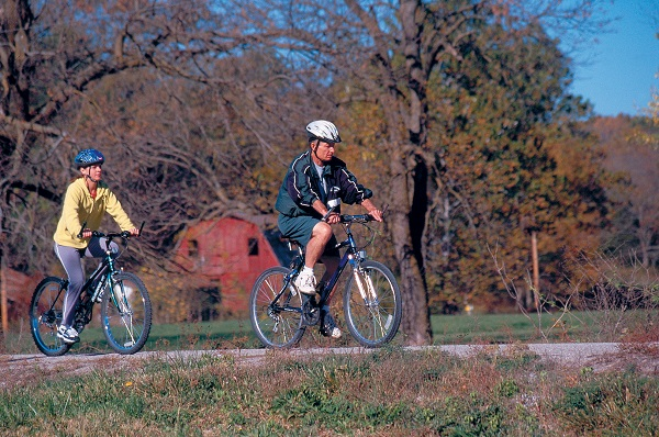 Two bicyclists riding past a barn on Katy Trail State Park