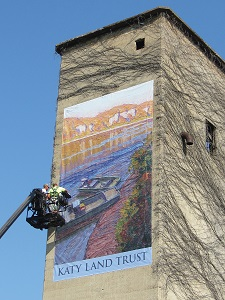 construction person on a lift puting up a Katy Land Trust banner