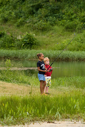 two kids fishing on the bank of the lake