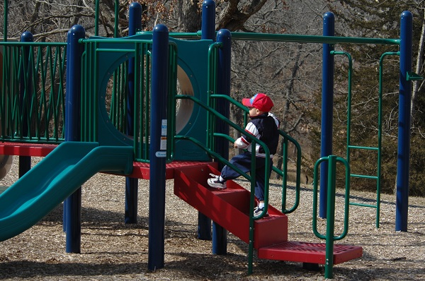 kid playing on playground equipment with slide