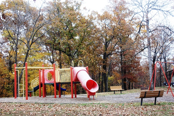 two benches next to the playground equipment with slides