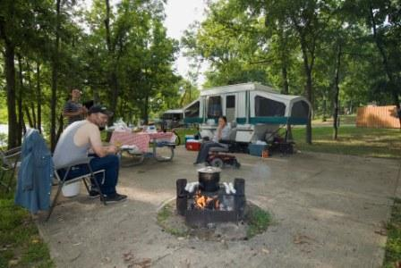 a couple cooking over their campfire with their picnic table and camper in the background